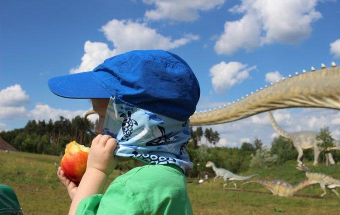 Dinopark Germendorf - Kind isst Apfel zwischen Dinosauriern