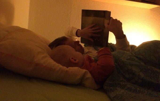 Kind liest mit Papa Buch im Bett