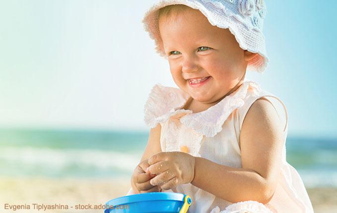 Kleines Kind mit Buddelzeug lächelnd am Strand
