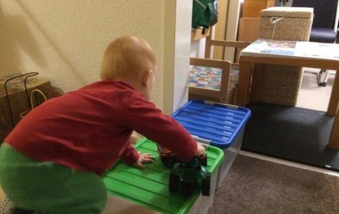 Kind klettert mit Spielzeug über Kisten