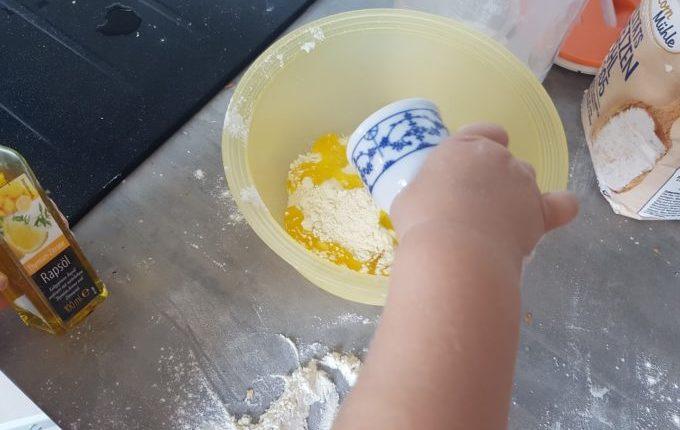 Kind füllt Rapsöl im Eierbecher in eine Schüssel mit Mehl