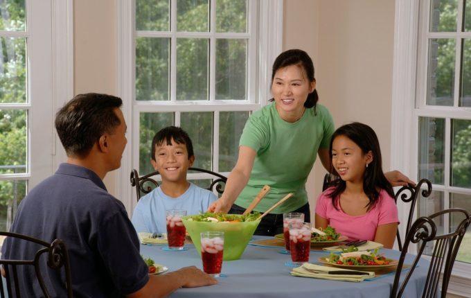 Tischmanieren der Kinder - Blogparade - glückliche Familie am Tisch und alle lächeln, Frau reicht Mann das Essen