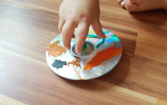 Kind dreht selbst bemalten Farbkreisel aus CD