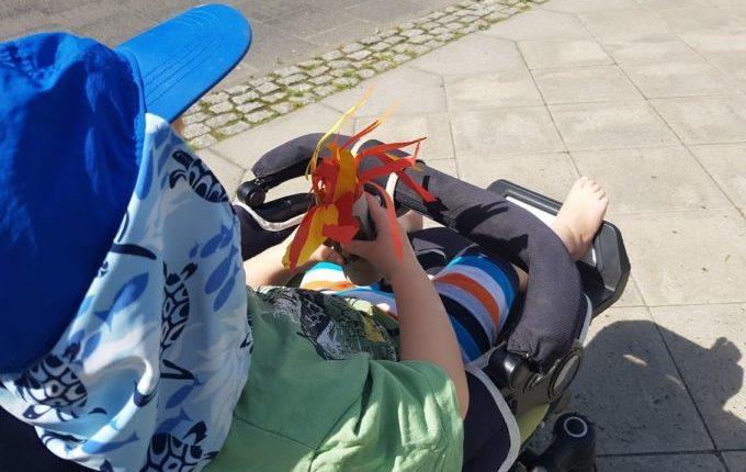 Kind im Kinderwagen hält Klopapier-Drache