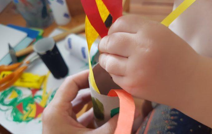 Kind klebt Streifen in Klopapierrolle