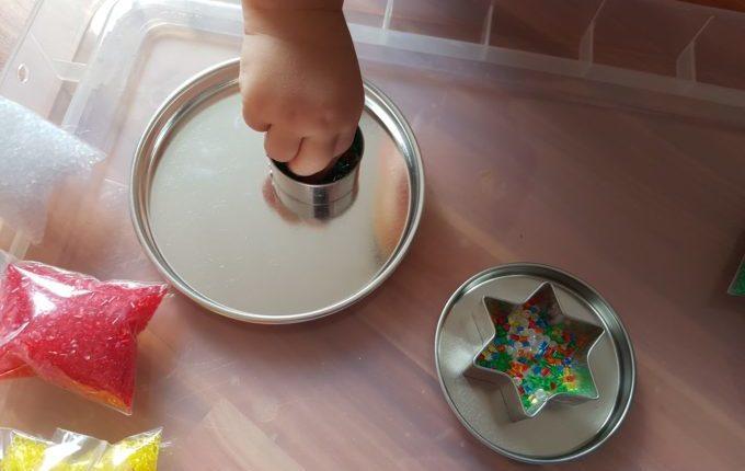 Kind legt Schmelzgranulat in Ausstechform