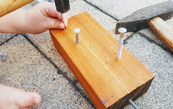 Kind schlägt Nagel mit Hammer in ein Stück Holz