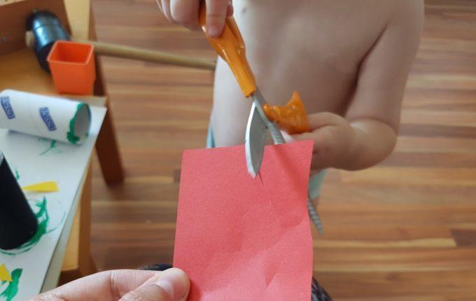 Kind schneidet rotes Papier mit der Schere