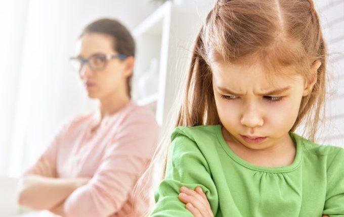 Kind und Mutter verschränken die Arme und schauen ernst
