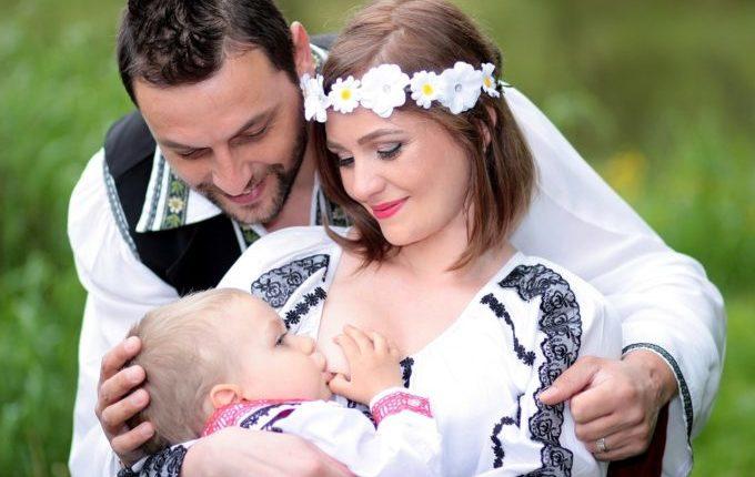 Braut stillt Kind, Bräutigam legt den Arm um sie und lächelt zum Kind