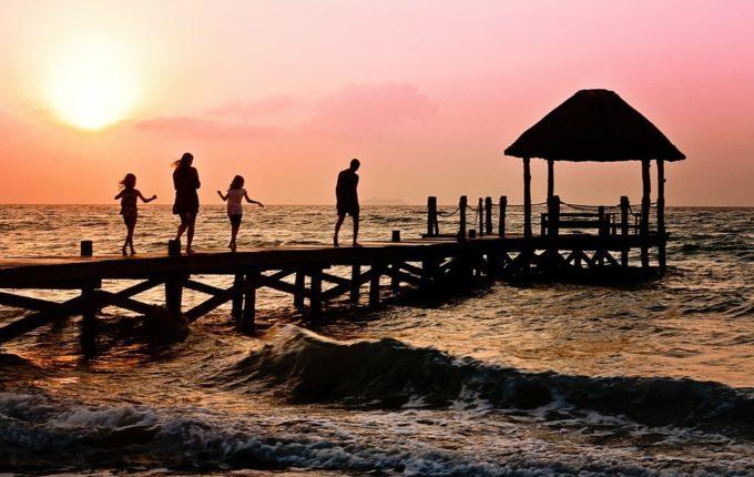 Familie bei Sonnenuntergang auf dem Steg