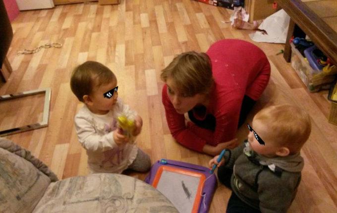 Frau spielt mit Kindern auf dem Boden und macht große Augen