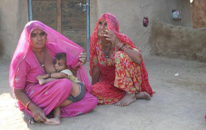 Frau stillt Kind auf dem Boden