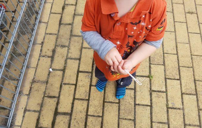 Kind läuft draußen mit Socken auf dem Gehweg