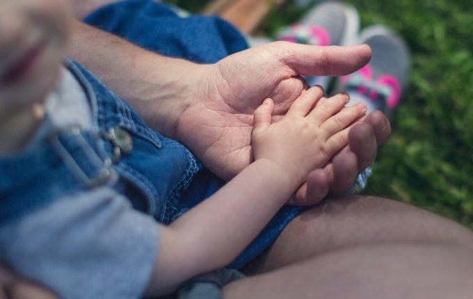 Kind legt seine Hand in die eines Erwachsenen