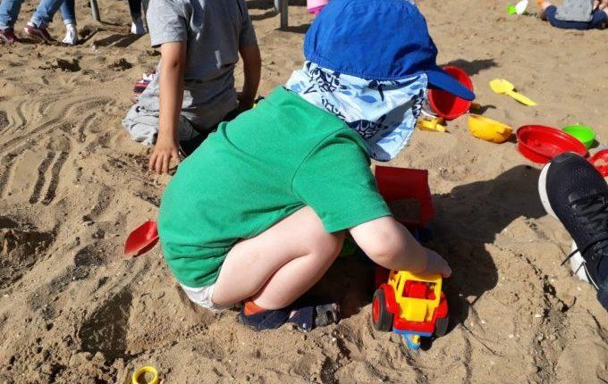 Kind spielt im Sandkasten mit fremdem Auto
