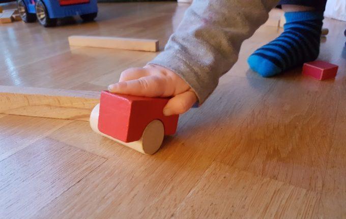 Kind spielt mit Auto aus zwei Bauklötzen
