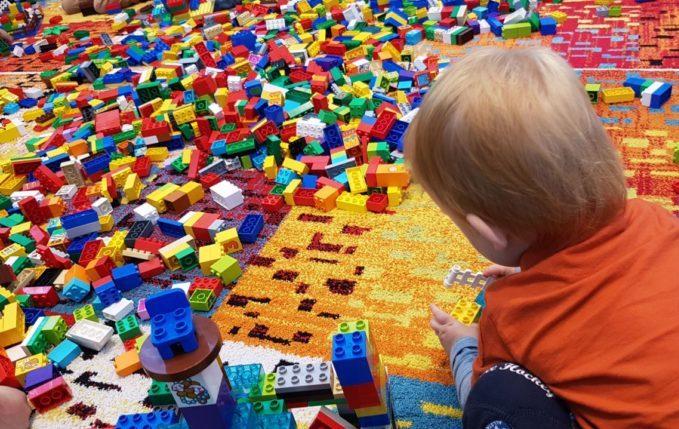 Kind spielt mit einem Berg aus Lego Duplo Bausteinen