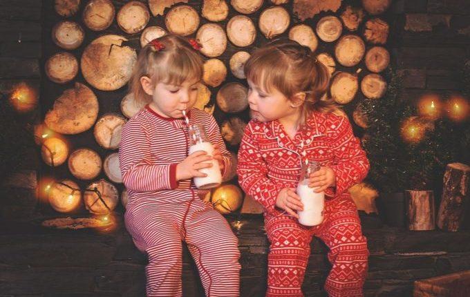 Kinder in Weihnachtskleidung trinken Milch aus Glasflaschen