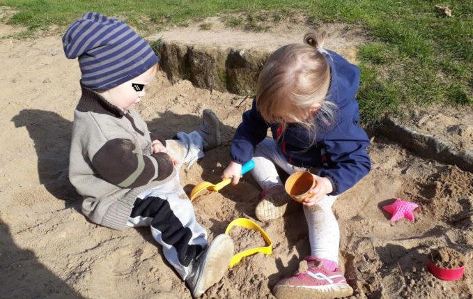 Kinder spielen gemeinsam im Sandkasten mit Buddelzeug