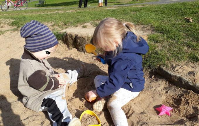 Kinder spielen zusammen im Buddelkasten