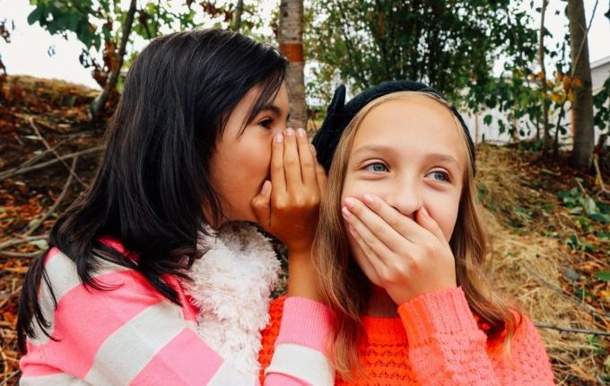 Kinder tuscheln und halten sich lachend die Hand vor den Mund