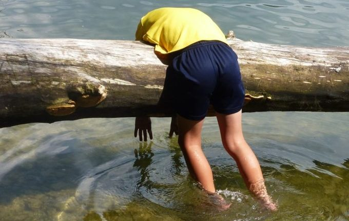 Mensch hängt schlapp über einem Baumstamm im Wasser