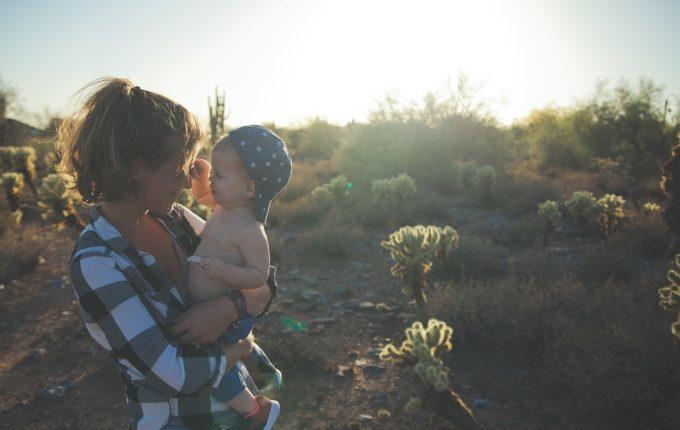 Mutter hält Kind in den Armen und lächelt es an