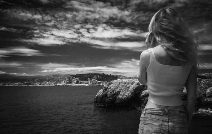 Frau schaut übers Meer auf Landschaft