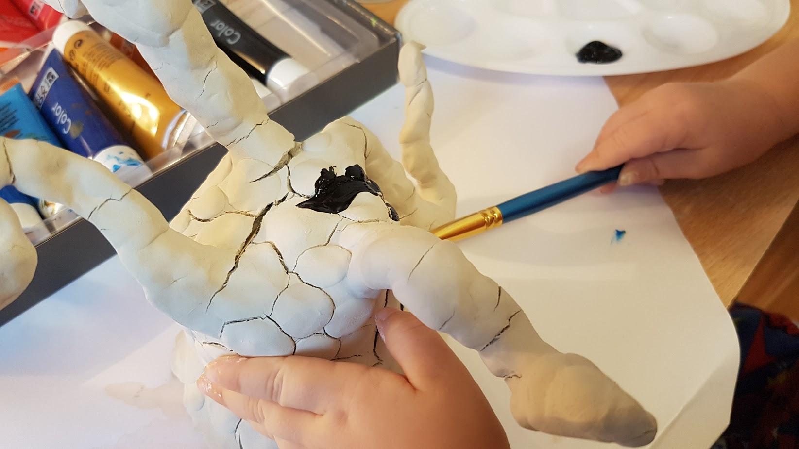 Kind bemalt Ton mit Acrylfarbe