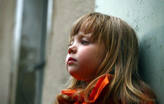 Kind lehnt traurig an einer Wand