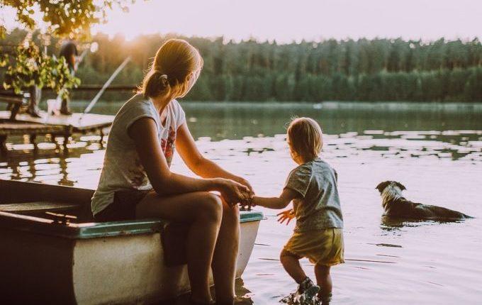 Mutter allein mit Kind und Hund am See