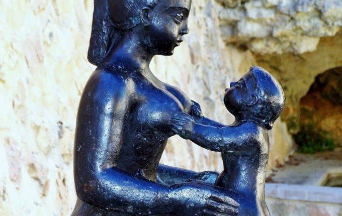 Statue - Kind hält Brüste von Mutter