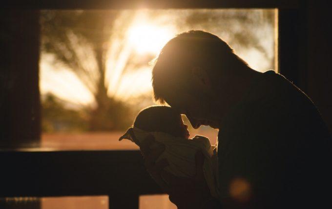 Vater Stirn an Stirn mit Baby im Arm