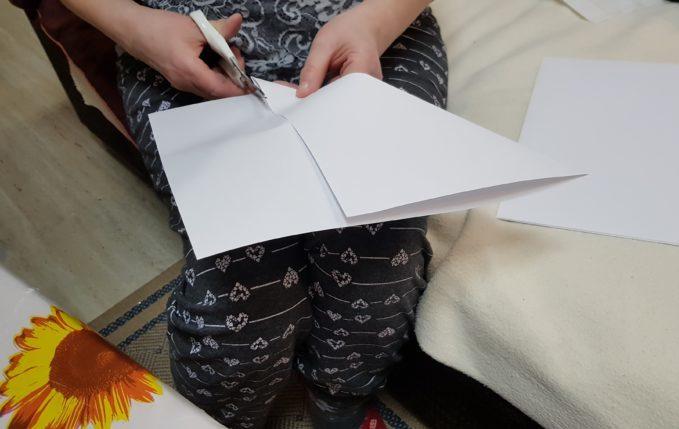Frau schneidet A4-Blatt quadratisch