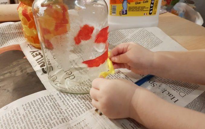 Kind beklebt Einmachglas mit Faserseide