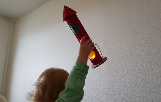 Kind hält Raketenlaterne hoch
