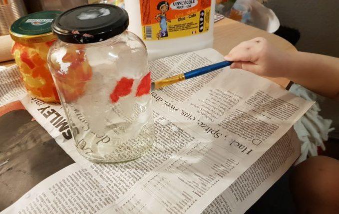 Kind pinselt Einmachglas mit Kleber ein