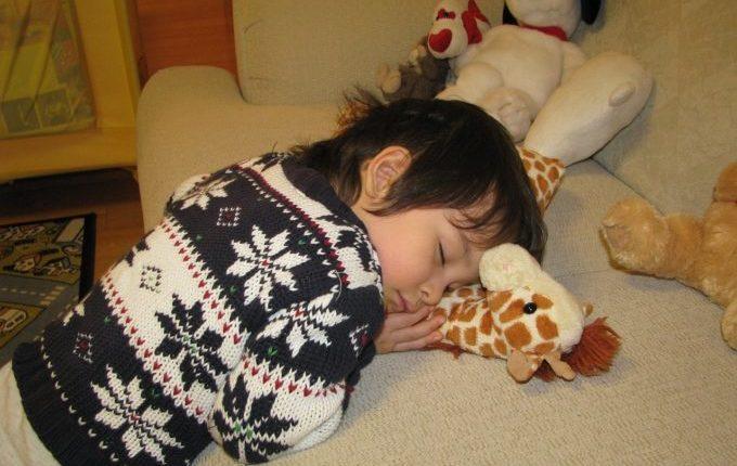Kind ist müde und schläft in Klamotten auf der Couch.jpg