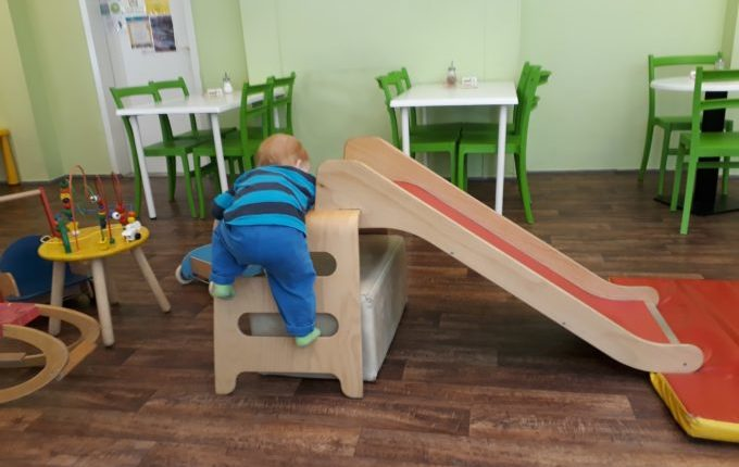 Kind klettert im Kindercafé auf Rutsche.jpg