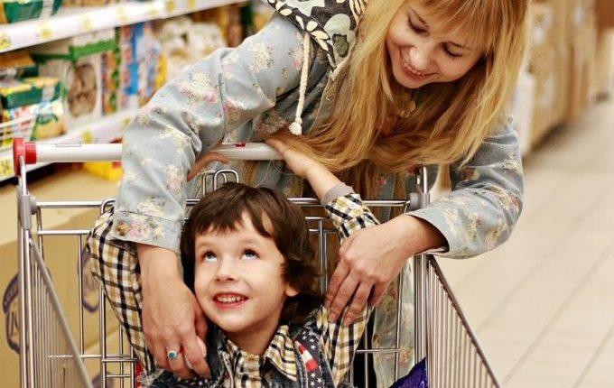 Mutter beugt sich zu Kind im Einkaufswagen.jpg