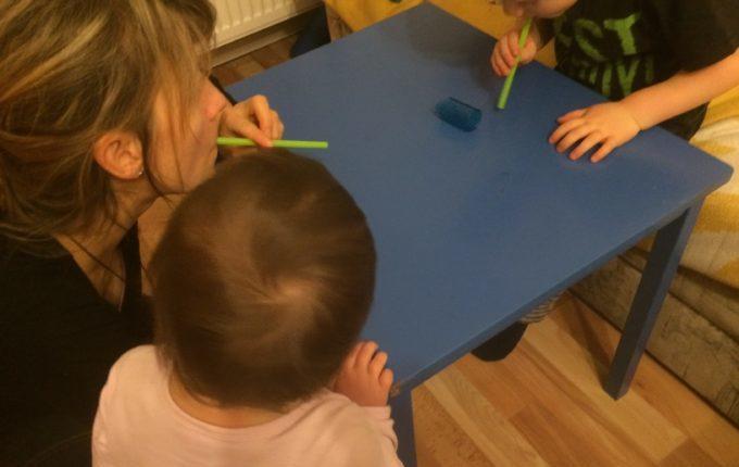 Mutter pustet Röllchen mit Strohhalm über den Tisch