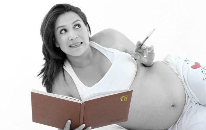 Schwangere überlegt mit Stift und Notizblock