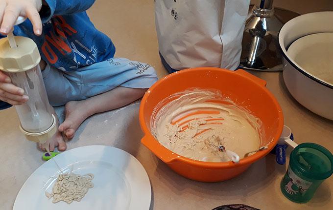 Kind spritzt Haferbrei auf Teller