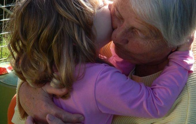 Kind umarmt und küsst alte Frau