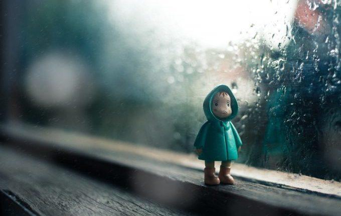 kleine Figur im Regenmantel steht allein am Fenster