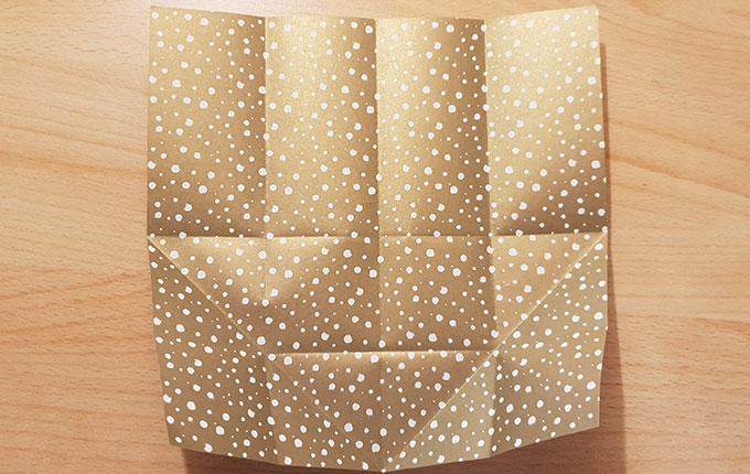 aufgefaltetes Origamipapier mit zahlreichen Falten und Diagonalen