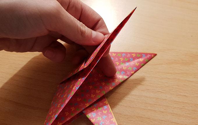 Finger nehmen anderen Flügel vom Origamipapier in die Hand