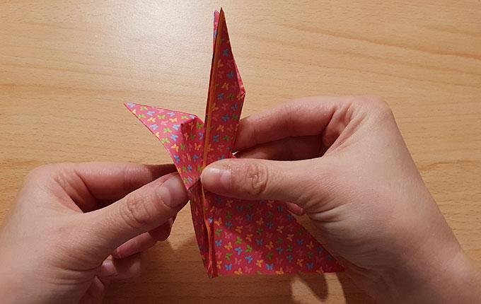 Hand hält Kopf und Ohren von Origamihasen fest