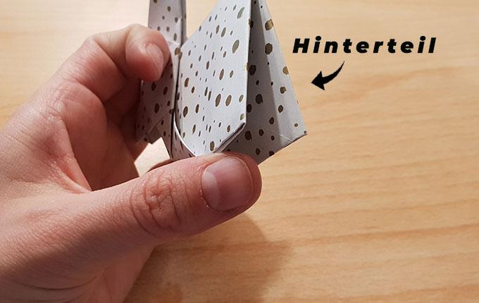 Hand hält Origamihasen Hinterteil von unten fest